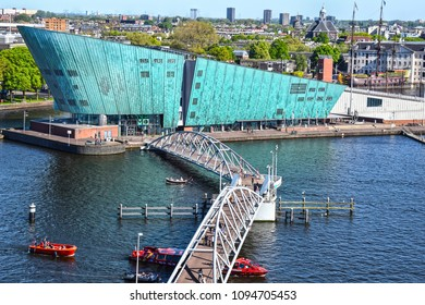 AMSTERDAM, NETHERLANDS - MAY 6, 2018: Science and Technology Museum NEMO on Oosterdok, Amsterdam, scheepvaartmuseum with the VOC-ship Amsterdam in background, attracting thousands of visitors