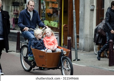 AMSTERDAM, NETHERLANDS - MAY 9: Father with two children  riding bicycles in historical part in Amsterdam, Netherlands on May 9, 2015