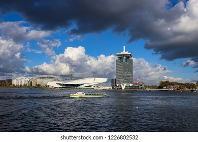 Amsterdam, Netherlands / November 03, 2018: Skyline of Amsterdam north, showing Amsterdam Tower, Eye Film Museum and a passing canal tour boat.