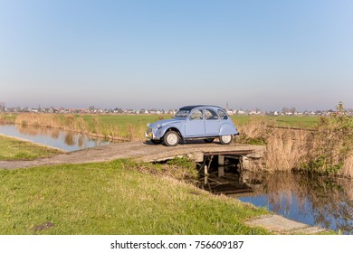 "AMSTERDAM, NETHERLANDS - NOVEMBER 10, 2017: A lavender blue Citroen 2CV ""Deux Cheveaux"" oldtimer car is parked in the green dutch polder with a bright blue autumn sun."
