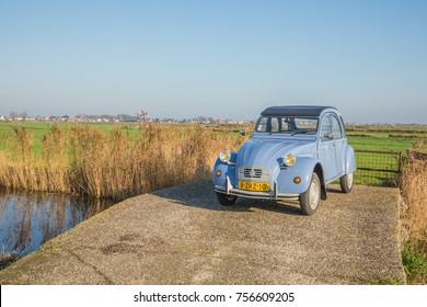 "AMSTERDAM, NETHERLANDS - NOVEMBER 10, 2017: A lavender blue Citroen 2CV ""Deux Cheveaux"" oldtimer car is parked in the green dutch polder with a bright blue autumn sun."