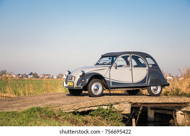 AMSTERDAM, NETHERLANDS - NOVEMBER 10, 2017: An antique oldtimer Citroen 2CV in Charleston version, is parked in the Dutch polder landscape under an autumn sun.