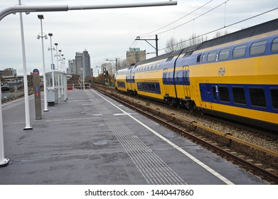 AMSTERDAM / NETHERLANDS - NOVEMBER 12 2010: A yellow and blue VIRM double-deck regional train operated by NS (Dutch Railways) roars past Van der Madeweg elevated station on an outer track.