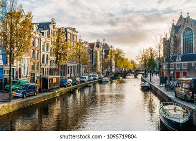 AMSTERDAM, NETHERLANDS - NOVEMBER 13, 2017: Beautiful Architecture Of Dutch Houses and Houseboats On Amsterdam Canal In Autumn