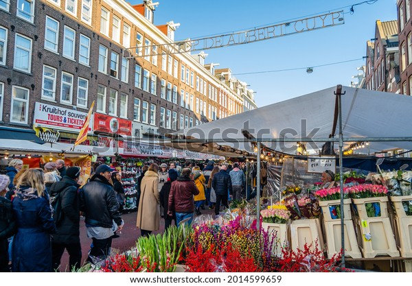 AMSTERDAM, THE NETHERLANDS - NOVEMBER 17, 2018: People visiting the Albert Cuyp Market, a street market and a tourist attraction in Amsterdam, on the Albert Cuypstraat in De Pijp area of the city