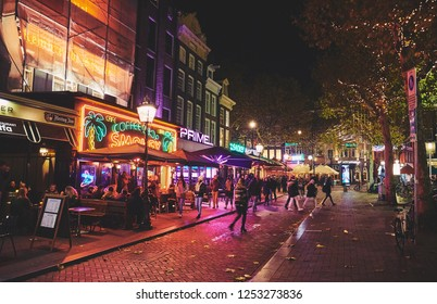 AMSTERDAM, NETHERLANDS - NOVEMBER 19, 2018: Restaurants, bars, cafes and coffeeshops on the streets in the city center at night.
