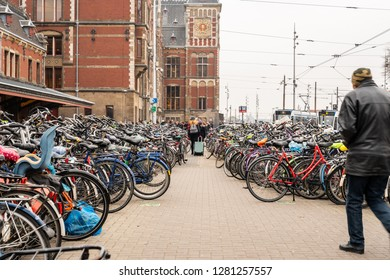 AMSTERDAM, NETHERLANDS - NOVEMBER 22,  2018: Outdoor perspective view of a large bicycle parking and people next to the Central train station in Amsterdam Netherlands November 22, 2018.