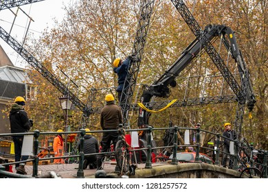 AMSTERDAM, NETHERLANDS - NOVEMBER 22,  2018: Outdoor closeup view of construction workers building and doing repairs on a city stone bridge in Amsterdam Netherlands November 22, 2018.