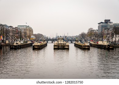 AMSTERDAM, NETHERLANDS - NOVEMBER 22,  2018: Winter scene. Front city view of sluice gates seen from the water with buildings in the background in Amsterdam Netherlands November 22, 2018.