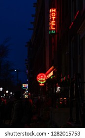 AMSTERDAM, NETHERLANDS - NOVEMBER 22, 2018: Perspective street night scene, building and neon lights and people on the street. Famous Red light District city nightlife in Amsterdam  November 22, 2018.