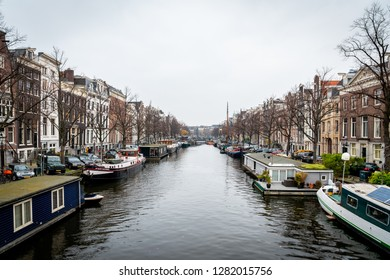 AMSTERDAM, NETHERLANDS - NOVEMBER 22,  2018:  Winter scene. Perspective city view of buildings and many houseboats on a canal in Amsterdam Netherlands November 22, 2018.
