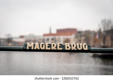 AMSTERDAM, NETHERLANDS - NOVEMBER 22, 2018: Selective focus of a bridge steel rail with a sign of the famous Magere Brug in Amsterdam Netherlands November 22, 2018. Buildings in the background.