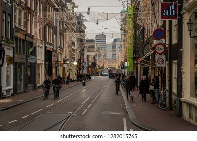 AMSTERDAM, NETHERLANDS - NOVEMBER 22,  2018:  Winter scene. Perspective street view of buildings, people and traffic on a Christmas decorated street  in Amsterdam Netherlands November 22, 2018.