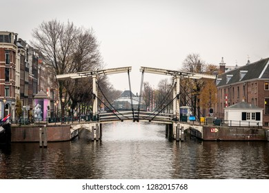 AMSTERDAM, NETHERLANDS - NOVEMBER 22,  2018: Winter scene. Side view of a famous wooden drawbridge seen from the water with buildings in the background in Amsterdam Netherlands November 22, 2018.