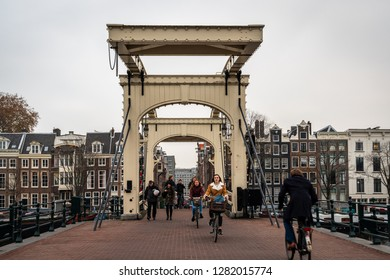 AMSTERDAM, NETHERLANDS - NOVEMBER 22,  2018: Front view of people passing the famous wooden drawbridge Magere Brug with buildings in the background in Amsterdam Netherlands November 22, 2018.