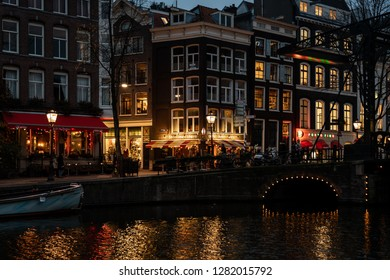 AMSTERDAM, NETHERLANDS - NOVEMBER 22,  2018: Night scene of water canal, buildings and neon lights and people on the street. Famous Red light District city nightlife in Amsterdam November 22, 2018.