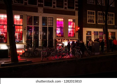 AMSTERDAM, NETHERLANDS - NOVEMBER 22,  2018: Night scene of water canal, building and neon lights and people on the street. Famous Red light District city nightlife in Amsterdam November 22, 2018.