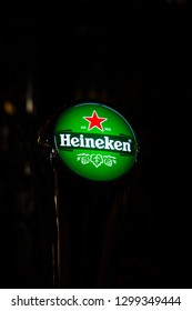 AMSTERDAM, NETHERLANDS - NOVEMBER 22, 2018: Closeup image of a beer tap with the Heineken brand sign illuminated in Amsterdam Netherlands November 22, 2018.