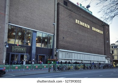 Amsterdam, Netherlands - November 24, 2016: Entry of the Heineken Brewery by Willem Kromhout, on the corner of the Stadhouderskade and the Ferdinand Bolsstraat, with pedestrians and bike riders.