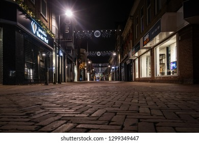 AMSTERDAM, NETHERLANDS - NOVEMBER 24, 2018: Low angle perspective night view of a empty Christmas decorated shopping street in Amsterdam Netherlands November 24, 2018.