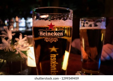 AMSTERDAM, NETHERLANDS - NOVEMBER 24, 2018: Closeup image of a glass of beer with the Heineken brand sign illuminated in Amsterdam Netherlands November 24, 2018. Incidental people in the background.