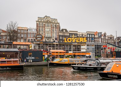 AMSTERDAM, NETHERLANDS - NOVEMBER 25, 2018: Outdoor city view of Lovers Canal Cruises pickup location with incidental people and many boats in the foreground in Amsterdam Netherlands November 25, 2018