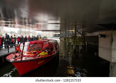 AMSTERDAM, NETHERLANDS - NOVEMBER 25, 2018:  People waiting in line at a canal cruise pickup location. A river cruise boat in the foreground moored at concrete boathouse in Amsterdam November 25, 2018