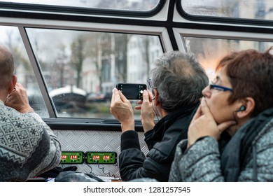 AMSTERDAM, NETHERLANDS - NOVEMBER 25, 2018: Inside view of boat with three older tourists, in a canal cruise boat looking out of a window taking photograph of the city in Amsterdam November 25, 2018.