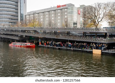 AMSTERDAM, NETHERLANDS - NOVEMBER 25, 2018: Front view of many people waiting in line by the water at a canal boat cruise pickup location next to a bicycle parking house in Amsterdam November 25, 2018