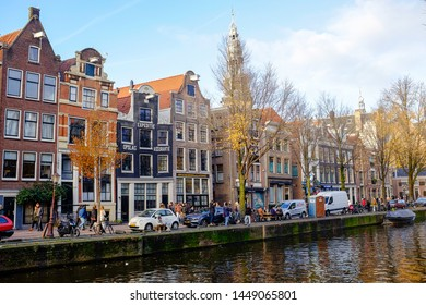 Amsterdam, Amsterdam, Netherlands - November 26 2016 : Amsterdam traditional canal multicolored buildings architecture with water reflections and boats over cloudy sky, holland Europe capital
