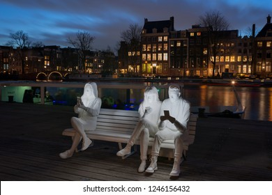 Amsterdam, The Netherlands - November 30, 2018: Amsterdam during Amsterdam Light festival along the river Amstel with artwork Absorbed by Light of Gali May Lucas (UK), smartphone users with faces lit