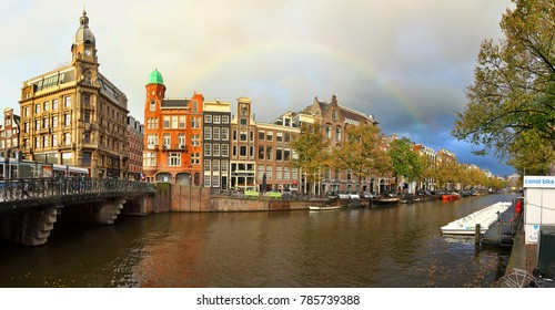 AMSTERDAM, NETHERLANDS - OCTOBER 08, 2014 : Amsterdam canal street view with bridge, bicycles parking, canal bike rent station. Cafe on waterfront. Moored boats. Fall yellow foliage. Rainbow in sky