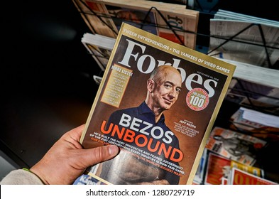 AMSTERDAM, NETHERLANDS - OCTOBER 08, 2018: Forbes magazine with Jeff Bezos on the cover in a hand. Jeff Bezos is president of Amazon. Forbes is an American family-controlled business magazine.