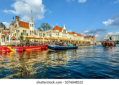 Amsterdam, Netherlands - October 1 2015: Tourists crowd a tour boat in front of an open air cafe alongside the canal with the Central Train Station behind