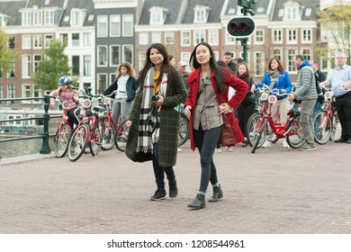 Amsterdam, The Netherlands - October 20, 2018: People (two beautiful woman) and bicycles on the Skinny Bridge (Magere Brug) over the river Amstel.