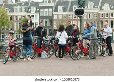 Amsterdam, The Netherlands - October 20, 2018: group of tourists and tour guide on Skinny Bridge (Magere Brug) Amsterdam over the river Amstel.