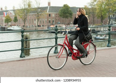Amsterdam, The Netherlands - October 20, 2018: woman riding (and on the phone) on a red bike, Skinny Bridge/Magere Brug. Hermitage Amsterdam in the background.