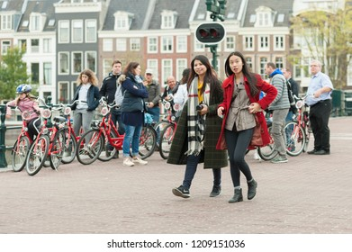 Amsterdam, The Netherlands - October 20, 2018: People (also two Asian women)and bicycle on the Skinny Bridge (Magere Brug) over the river Amstel.