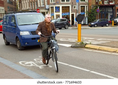 AMSTERDAM, NETHERLANDS - OCTOBER 23, 2014. Elegantly dressed middle-aged man riding a bicycle in historical town. Bridge Blauwbrug, Amsterdam, the Netherlands.