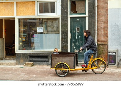 AMSTERDAM/ NETHERLANDS - OCTOBER 23, 2014. Father with a child in the cargo bicycle in the downtown of Amsterdam, Netherlands.