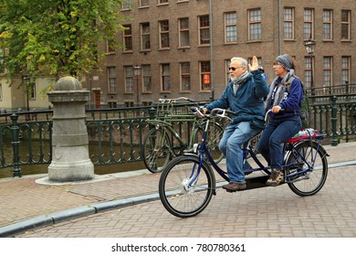 AMSTERDAM/ NETHERLANDS - OCTOBER 25, 2014.  An elderly couple riding the tandem bike in the historical center. The intersection of the Prinsengracht and Leidsegracht canal, Amsterdam, the Netherlands.