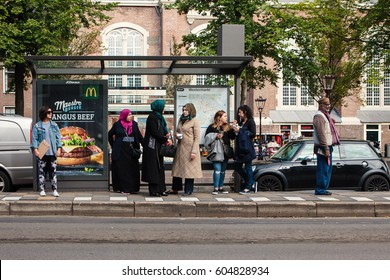 Amsterdam, Netherlands - October 3, 2016: People of different ethnic groups are waiting in a public transport station. Multicultural diversity issue.