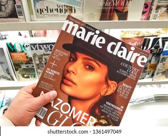 AMSTERDAM, NETHERLANDS: - OCTOBER 8, 2018: Marie Claire magazine in a hand over a stack of magazines. Marie Claire, international magazine first published in France