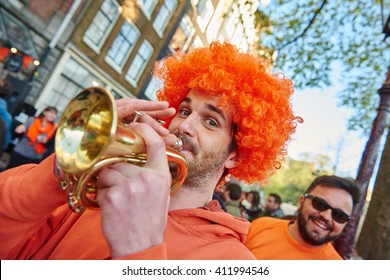 AMSTERDAM, NETHERLANDS  on APRIL 26, 2015. Portrait of happy male city native tourist with orange color hair and horn celebrating Queen's Day or King's day, Dutch annual national Holland holiday