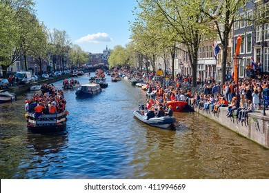 AMSTERDAM, NETHERLANDS on APRIL 26, 2015. City natives and tourists celebrate Queen's Day or King's day, Dutch annual national holiday, in cruiseboat on canal river of Amsterdam, Holland