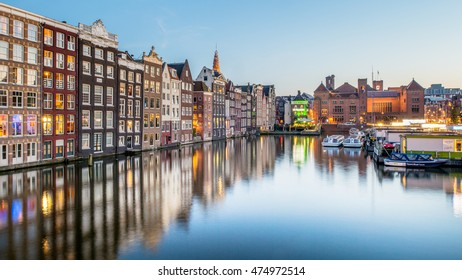 AMSTERDAM, THE NETHERLANDS ON AUGUST 25, 2016: Colorful view of the Damrak at dusk. Amsterdam is the capital and most populous city in Netherlands.