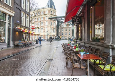 AMSTERDAM, NETHERLANDS on MARCH 28, 2016. Typical urban view in the spring evening. Little tables of summer cafe on the sidewalk.