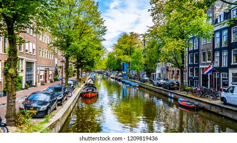 Amsterdam, the Netherlands - Sept 28, 2018: Small boats, cars and bikes lining the Elegantiersgracht canal in the historic Jordaan district in the old center of Amsterdam