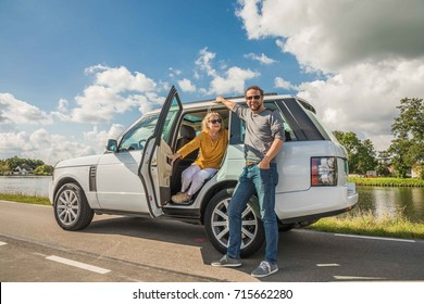 AMSTERDAM, NETHERLANDS - SEPTEMBER 02, 2017: Family of mother and son posing in a Fuji white SUV Landrover Range Rover Vogue 2011 model parked at a roadside during summer