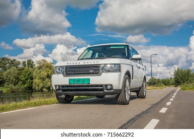 AMSTERDAM, NETHERLANDS - SEPTEMBER 02, 2017: Fuji white SUV Landrover Range Rover Vogue 2011 model parked at a small road in the dutch polder during a summer day with blue sky and white clouds
